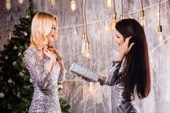 Twee mooie meisjes, brunette en blondevrouwen die elkaar Kerstmisgiften geven royalty-vrije stock afbeelding