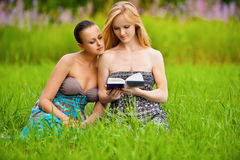 Twee mooie meisjes die boek lezen Stock Afbeelding
