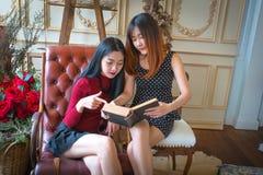 Twee mooie meisjes die boek lezen Stock Foto's