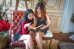 Twee mooie meisjes die boek lezen Stock Afbeeldingen