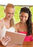 Twee mooie meisjes die de computer van tabletpc in koffie buiten bekijken Stock Fotografie