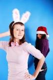 Twee mooie meisjes die de kleren van de Kerstman dragen. Royalty-vrije Stock Afbeeldingen