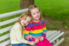 Twee mooie meisjes die in de tuin stellen Stock Fotografie