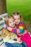 Twee mooie meisjes die in de tuin stellen Stock Afbeeldingen