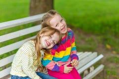 Twee mooie meisjes die in de tuin stellen Stock Foto