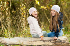 Twee Mooie meisjes die een baretzitting bij logboek het stellen dragen Royalty-vrije Stock Afbeeldingen