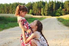 Twee mooie meisjes die en bij het gebied in w glimlachen spelen royalty-vrije stock foto