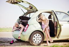 Twee mooie meisjes die in gebroken auto zitten en op hulp wachten Stock Fotografie