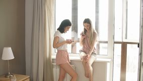Twee mooie meisjes die hun smartphones met behulp van stock video