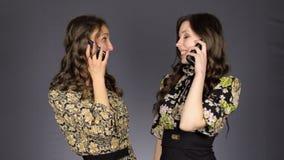 Twee mooie meisjes die op de telefoon spreken stock videobeelden