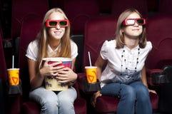 Twee mooie meisjes die op een film letten bij de bioskoop Stock Fotografie