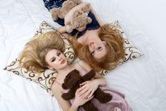 Twee mooie meisjes die op pilloows liggen Royalty-vrije Stock Afbeeldingen