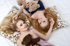 Twee mooie meisjes die op pilloows liggen Royalty-vrije Stock Foto