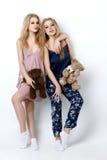 Twee mooie meisjes die op pilloows liggen Stock Foto