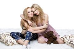 Twee mooie meisjes die in pyjama's zitten Royalty-vrije Stock Foto's