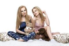 Twee mooie meisjes die in pyjama's zitten Stock Afbeelding