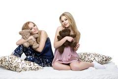 Twee mooie meisjes die in pyjama's zitten Royalty-vrije Stock Afbeeldingen