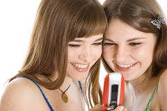 Twee mooie meisjes die SMS op mobiele telefoon lezen Stock Foto