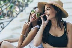 Twee mooie meisjes die terwijl het spreken op telefoon lachen Stock Foto's