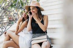 Twee mooie meisjes die terwijl het spreken op telefoon lachen Stock Foto