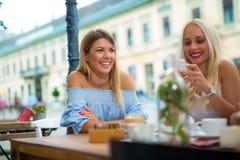 Twee mooie meisjes die terwijl het zitten in een bar lachen stock foto's