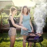 Twee mooie meisjes die voedsel bij de grill maken stock afbeelding