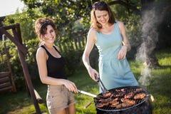Twee mooie meisjes die voedsel bij de grill maken royalty-vrije stock afbeelding