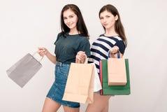 Twee mooie meisjes die zich met het winkelen zakken bevinden en gelukkig het glimlachen Stock Afbeelding