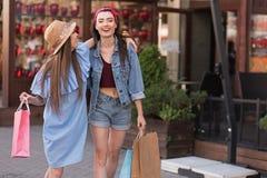 Twee mooie meisjes die zich op de straat met zakken bevinden Stock Afbeeldingen