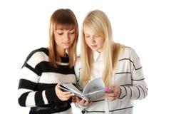 Twee mooie meisjes gelezen agendaboek Stock Afbeeldingen