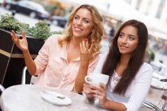Twee mooie meisjes in koffie Stock Foto