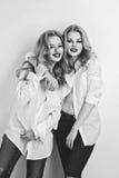 Twee mooie meisjes in mensenoverhemden en jeans Stock Foto