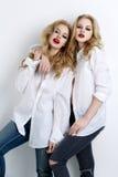 Twee mooie meisjes in mensenoverhemden en jeans Stock Fotografie