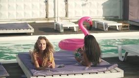 Twee mooie meisjes met coctails in mooie swimwear hebben vrolijk gesprek op het zitkamer dichtbij zwembad stock videobeelden