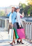 Twee mooie meisjes met het winkelen zakken het tonen beduimelt omhoog Royalty-vrije Stock Fotografie