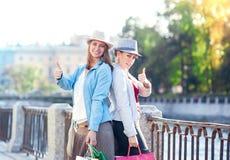 Twee mooie meisjes met het winkelen zakken het tonen beduimelt omhoog Royalty-vrije Stock Afbeelding