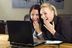 Twee mooie meisjes met laptop in het bureau stock afbeeldingen