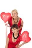 Twee mooie meisjes met rode hartballon stock foto