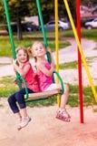 Twee mooie meisjes op een schommeling openlucht in de speelplaats Royalty-vrije Stock Foto
