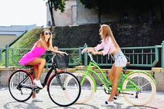 Twee mooie meisjes op fietsen - openlucht Royalty-vrije Stock Afbeelding