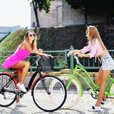 Twee mooie meisjes op fietsen - openlucht Stock Foto