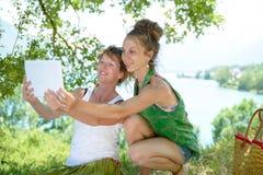 Twee mooie meisjes op het gras met een digitale tablet Royalty-vrije Stock Foto's