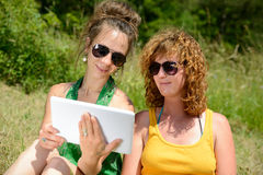 Twee mooie meisjes op het gras met een digitale tablet Stock Foto