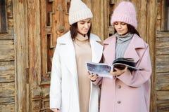 Twee mooie meisjes in openlucht gelezen tijdschrift en glimlach stock afbeelding