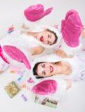 Twee mooie meisjes in wit rood kostuum die op de vloer liggen Royalty-vrije Stock Foto