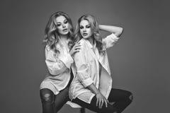 Twee mooie meisjes in witte overhemden en jeans Royalty-vrije Stock Afbeelding