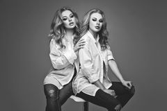 Twee mooie meisjes in witte overhemden en jeans Stock Afbeeldingen