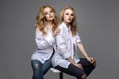 Twee mooie meisjes in witte overhemden en jeans Stock Fotografie