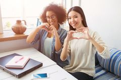 Twee mooie meisjes zitten samen op bank Zij zijn studenten De jonge vrouwen heeft wat tijd voor rust zij zijn stock afbeeldingen