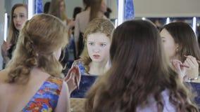 Twee mooie meisjes zitten voor spiegel en zijn toepassen schoonheidsmiddelen van hun gezichten stock videobeelden